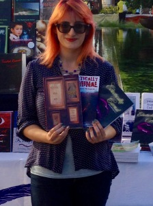 Holding the three anthologies that contain my five short stories